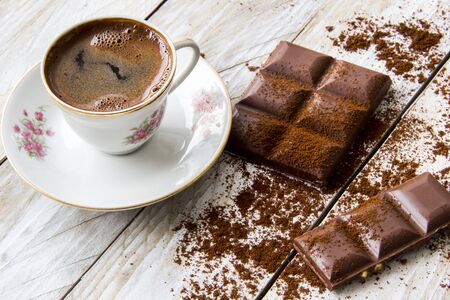 Turkish coffee with slices of chocolate on the wooden table