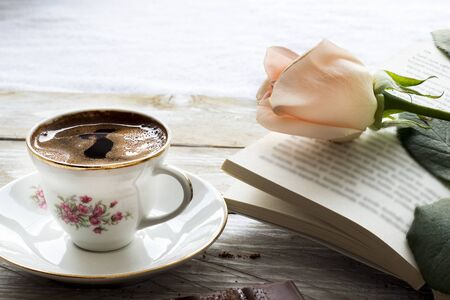 Turkish coffee with peach-colored rose, slices of chocolate and book on the wooden table Stock Photo