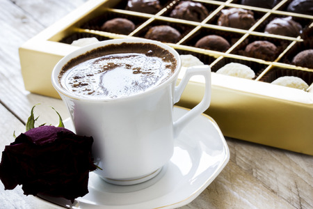Turkish coffee, truffle chocolate and dried rose on wooden table Stock Photo