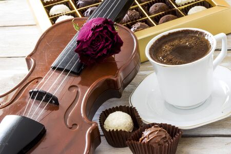 Turkish coffee, truffle chocolate and violin on wooden table Stock Photo