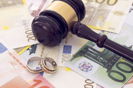 Family law concept, gavel, rings and money on wooden table