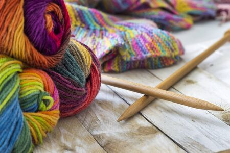 Colorful skeins of wool with knitting needles and sweater on wooden background