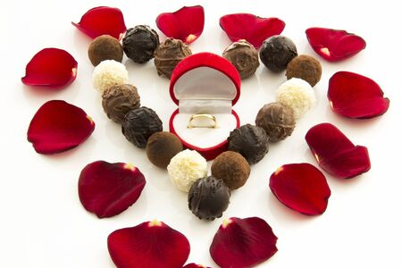 Heart-shaped gift box of truffles and wedding rings in red rose petals among Stock Photo