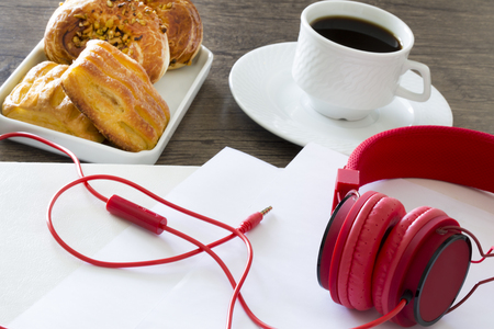 Office workplace. Croissants on wooden table with coffee and headsets
