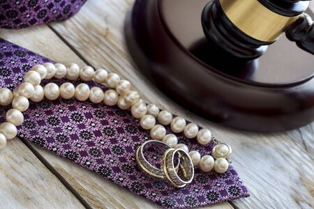 judicature: Divorce law concept. Judge gavel, rings, tie and pearl necklace