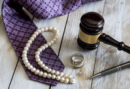 Divorce law concept. Judge gavel, rings, tie and pearl necklace