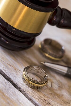 judicature: Divorce concept. Close up of wedding rings and judge gavel Stock Photo
