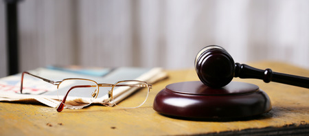 Labor law concept, gavel, glasses and newspaper on wooden table