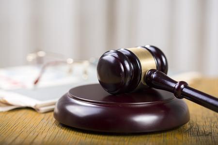 Arbeidsrecht concept, hamer, bril en krant op houten tafel Stockfoto