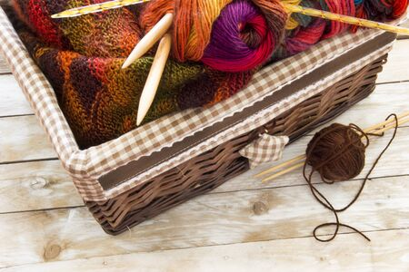 Colorful wood skeins of wool and knitting needles in a basket on wooden table