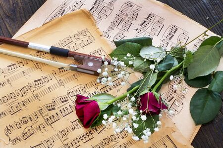 Violin, red roses and music notes on wooden table
