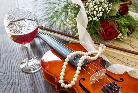 Violin, wine, red roses and music notes on wooden table