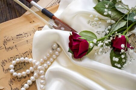 Violin, red rose, pearl necklace and music notes on satin fabric