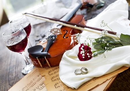 Violin, red rose, marriage rings, wine and music notes on satin fabric Stock Photo