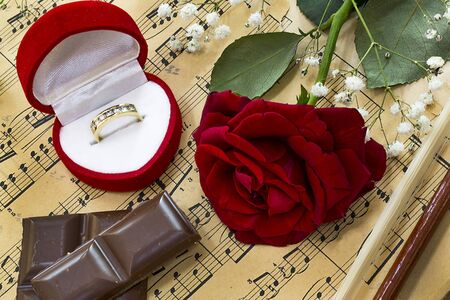 Marriage rings, red rose, chocolate chips and violin on music notes Stock Photo