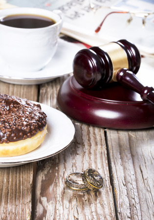 Family law concept. Gavel, newspaper and coffee on wooden table Stock Photo