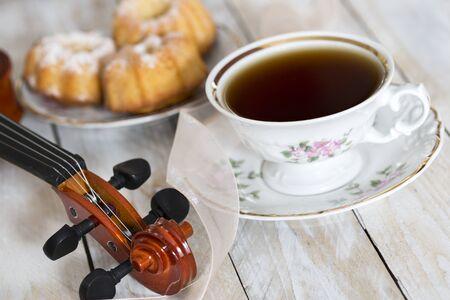 Káva s košíčky a housle na dřevěném stole