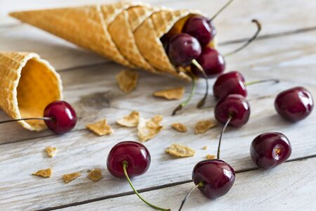 cornet: Waffle cones and cherry on the wood