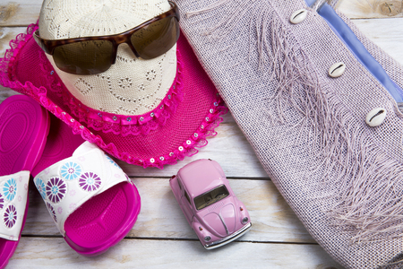 Pair of slippers, pink straw hat and beach bag on wood. Vacation in summer
