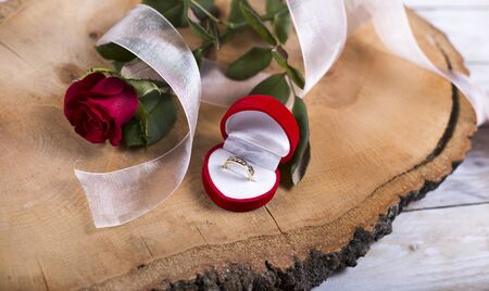 flyaway: Marriage proposal with golden ring and red rose on wooden