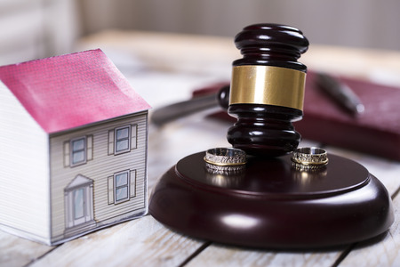 Family law concept. Divorce. Gavel, house and rings