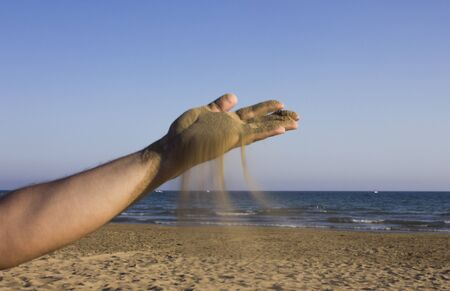 flowing water: Sea sand flowing through a mans hands