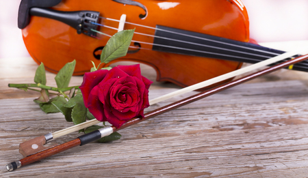 Violin and red rose on wooden table