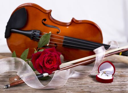 Marriage proposal with gold ring, red rose and violin on wooden table