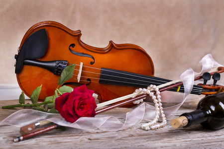 Violin, red rose, pearl necklace and wine on wooden table