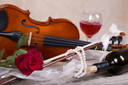 valentines day mother s: Violin, red rose, pearl necklace and wine on wooden table
