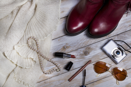 Leather woman boots, pearl necklace and accessory on wooden background