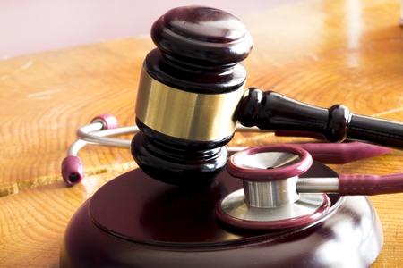 Medical law concept. Gavel and stethoscope on wooden table Banque d'images