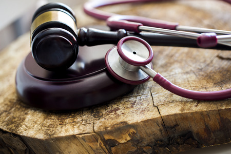 Medical law concept. Gavel and stethoscope on wooden table Stockfoto
