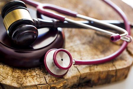 Medical law concept. Gavel and stethoscope on wooden table Stock Photo