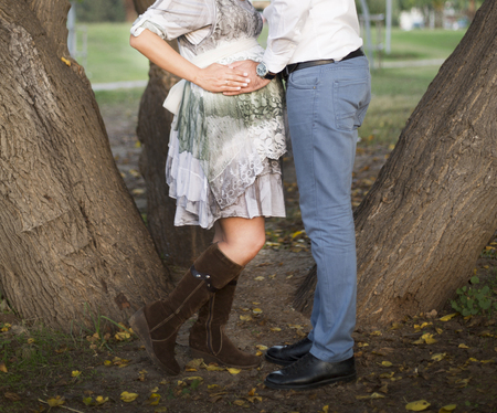 Happy couple huging in nature. Pregnant Belly