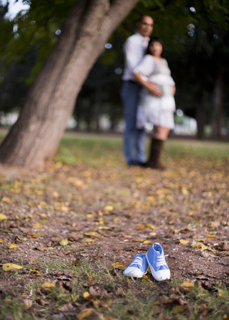 Baby shoes on blue background Happy couple having fun Stockfoto