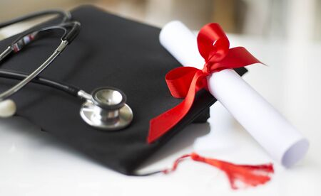 Black graduation cap, degree and stethoscope