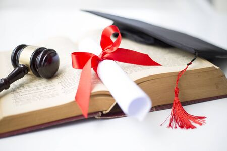 Black graduation cap, degree and gavel