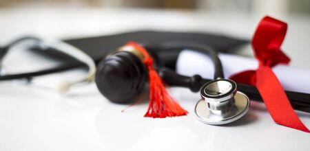 Black graduation cap, stethoscope and gavel Stockfoto