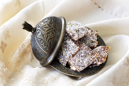 Traditional turkish dessert cezerye and copper serving set. Coffee or tea is served with cezerye. Feast of Ramadan. Cezerye is made with boiled carrots, sugar, pistachio and coconut. It is located dessert of Adana and Mersin cities in Turkey.