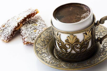 Turkish coffee with traditional turkish dessert cezerye and copper serving set. Feast of Ramadan. Cezerye is made with boiled carrots, sugar, pistachio and coconut. It is located dessert of Adana and Mersin cities in Turkey.