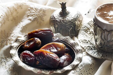 Dried dates with coffee and traditional silver serving set. Feast of Ramadan.
