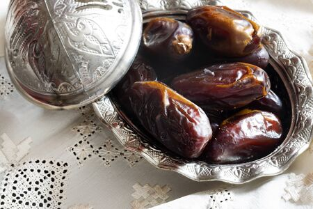Dried dates and traditional silver serving set. Feast of Ramadan.