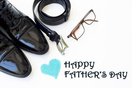 Father's Day Concept. Black Patent Leather Shoes, Tie, Belt, Eyeglasses and heart on a white background. Copy space for text