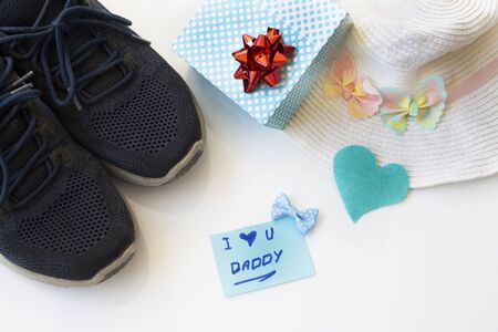 Father's Day Concept. Gift box with sport shoes, hat and greeting card with heart on a white background. Copy space for text. Father's Daughter.
