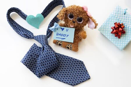 Father's Day Concept. Brown teddy bear with greeting card and tie on a white background. Copy space for text.