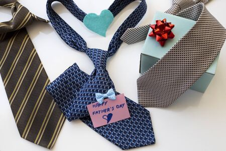Father's Day Concept. Ties, gift box and heart with greeting card on a white background. Copy space for text. Banque d'images