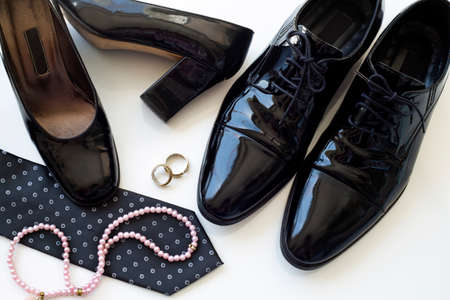Black man and woman patent leather shoes with wedding rings and pearl necklace on white background. Family law concept. Divorce. Wedding. Honeymoon.