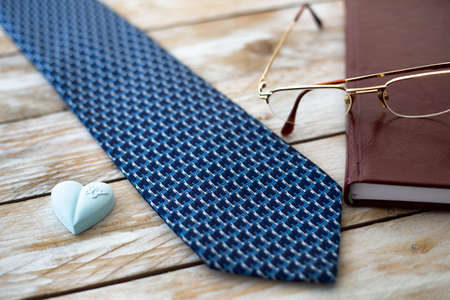 Father's Day Concept. Tie, Reading Glasses, diary and heart on wooden background. Copy space for text.