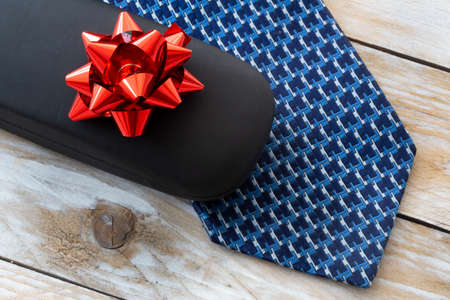 Father's Day Concept. Gift Box with Tie on wooden background. Copy space for text.